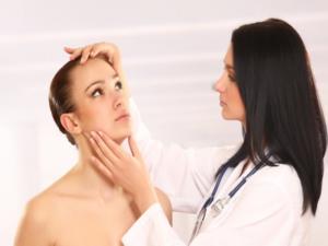 Consulta com Dermatologista, analisando a pele do rosto da paciente.