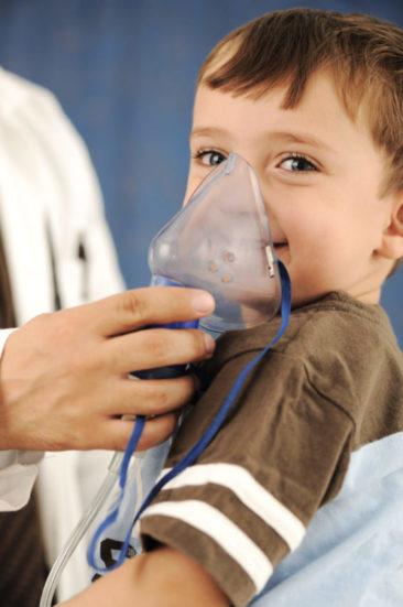 Criança fazendo inalação com máscara segurada por médico.